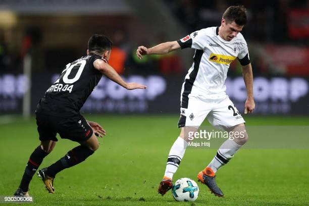 Charles Aranguiz of Bayer Leverkusen and Jonas Hofmann of Moenchengladbach battle for the ball during the Bundesliga match between Bayer 04...