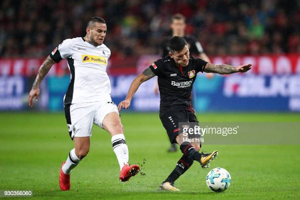 Charles Aranguiz of Bayer Leverkusen is chased by Raul Bobadilla of Moenchengladbach during the Bundesliga match between Bayer 04 Leverkusen and...