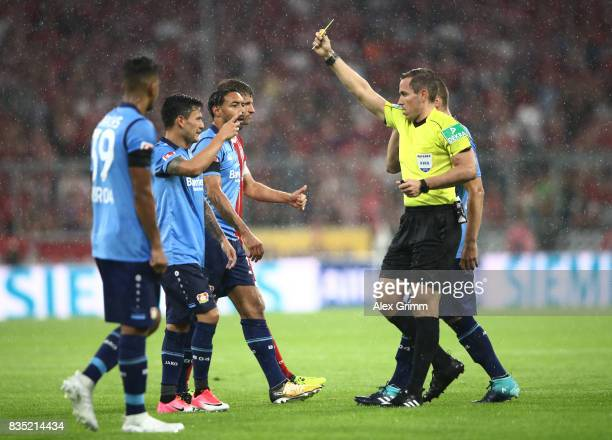 Charles Aranguiz of Bayer Leverkusen is shown a yellow card by referee Tobias Stieler during the Bundesliga match between FC Bayern Muenchen and...