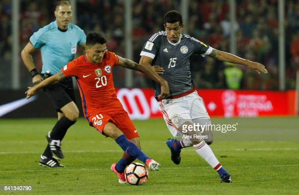 Charles Aranguiz of Chile fights for the ball with Victor Caceres of Paraguay during a match between Chile and Paraguay as part of FIFA 2018 World...