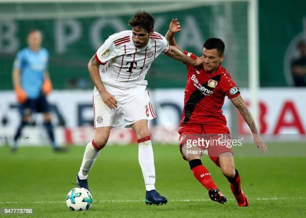 Charles Aranguiz of Leverkusen and Javier Martinez of Muenchen battle for the ball during the DFB Cup semi final match between Bayer 04 Leverkusen...