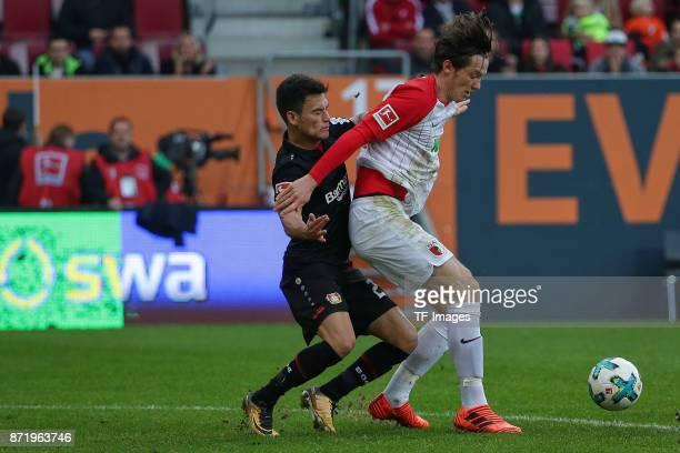 Charles Aranguiz of Leverkusen and Michael Grogoritsch of Augsburg battle for the ball during the Bundesliga match between FC Augsburg and Bayer 04...