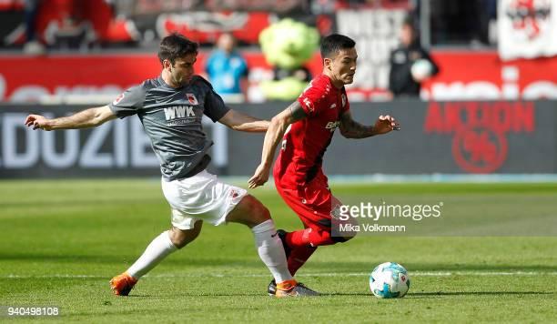 Charles Aranguiz of Leverkusen challenges Admir Mehmedi of Leverkusen during the Bundesliga match between Bayer 04 Leverkusen and FC Augsburg at...