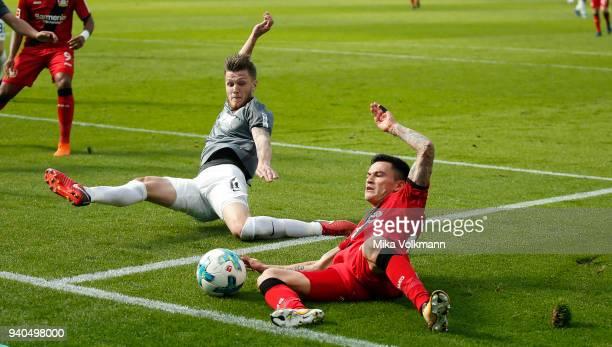 Charles Aranguiz of Leverkusen challenges Jeffrey Gouweleeuw of Augsburg during the Bundesliga match between Bayer 04 Leverkusen and FC Augsburg at...