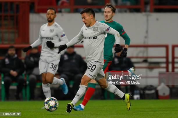 Charles Aranguiz of Leverkusen kicks the ball against Anton Miranchuk of Lokomotiv Moskva during the UEFA Champions League group D match between...