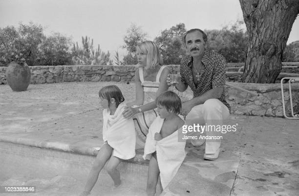 Charles Aznavour sitting with his wife Ulla Thorsell their daughter Katia and son Mischa by the pool in StTropez 15th July 1975