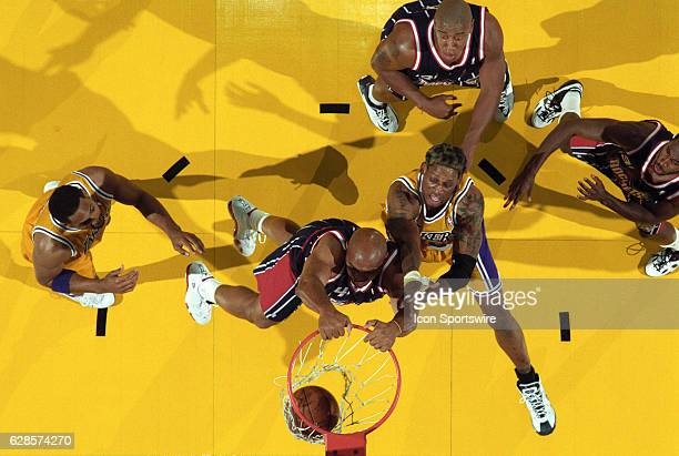 Charles Barkley of the Houston Rockets duns the ball as Dennis Rodman of the Los Angeles Lakers defends during a National Basketball Association game...