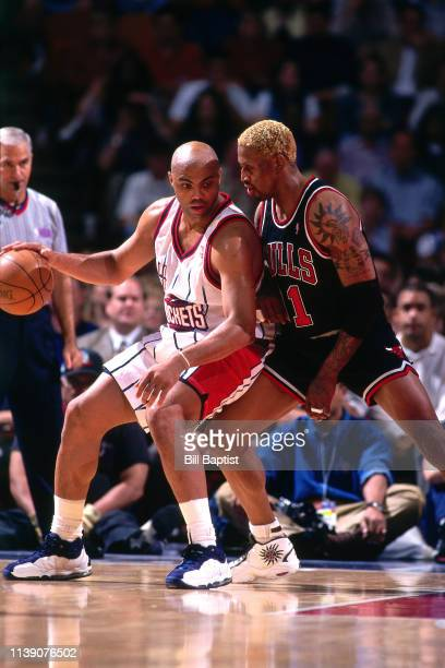 Charles Barkley of the Houston Rockets handles the ball against Dennis Rodman of the Chicago Bulls on April 5 1998 at The Summit in Houston Texas...