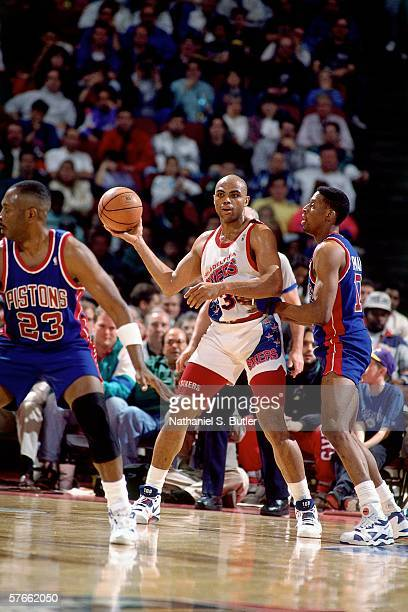 Charles Barkley of the Philadelphia 76ers looks to pass against Dennis Rodman of the Detroit Pistons during a game played in 1991 at the Spectrum in...