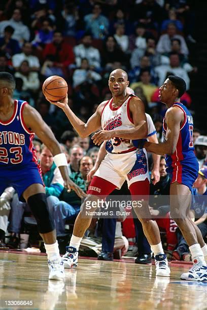 Charles Barkley of the Philadelphia 76ers passes against Dennis Rodman of the Detroit Pistons circa 1991 at the Spectrum in Philadelphia Pennsylvania...