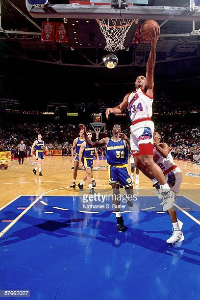 Charles Barkley of the Philadelphia 76ers shoots a layup against Tyrone Hill of the Golden State Warriors during a game circa 1991 at the Spectrum in...