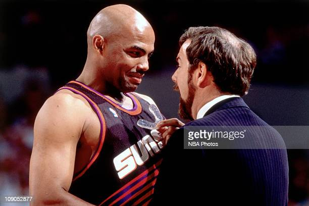 Charles Barkley of the Phoenix Suns shares a moment with Portland Trail Blazers coach PJ Carlisemo during a game played circa 1995 at Memorial...
