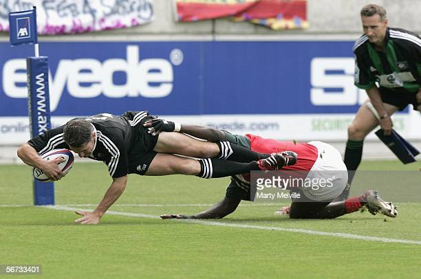 Charles Baxter from New Zealand scores the first try of the match as he is tackled by Kenya's Allan Makaka during the IRB sevens pool match between...