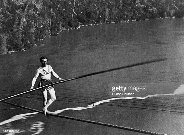 Charles Blondin, the French acrobat, performs a tightrope walk high above the Niagara River.