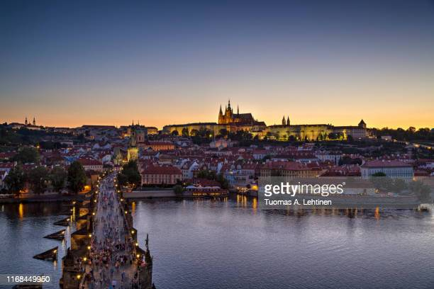 charles bridge and prague castle in prague at dusk - hradcany castle stock pictures, royalty-free photos & images