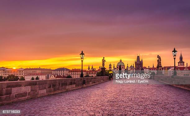 charles bridge by historic buildings in city against orange sky during sunset - charles bridge stock photos and pictures