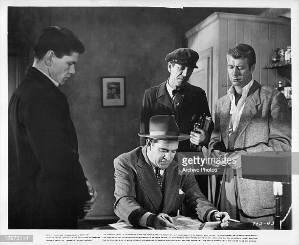 Charles Bronson and Gene Nelson standing over Ted de Corsia in a scene from the film 'Crime Wave' 1954