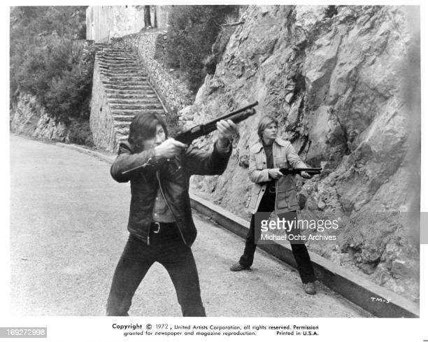 Charles Bronson and JanMichael Vincent aiming guns in a scene from the film 'The Mechanic' 1972
