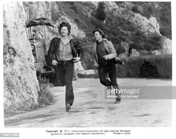 Charles Bronson and JanMichael Vincent running down road in a scene from the film 'The Mechanic' 1972
