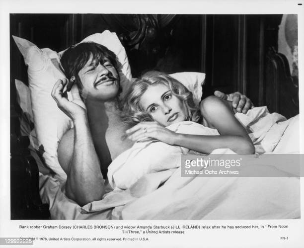 Charles Bronson And Jill Ireland relax in bed in a scene from the film 'From Noon Till Three' 1976