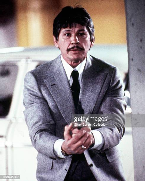 Charles Bronson US actor aiming a handgun in an image issued as publicity for the film 'Murphy's Law' USA 1986 The thriller directed by J Lee...