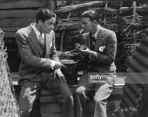 Charles 'Buddy' Rogers the American leading man looks concerned as his fellow Paramount player Richard Arlen goes to light a match near a can of gun...