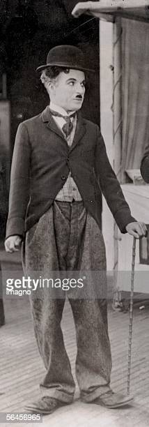 Charles Chaplin English actor and director Charlie Chaplin as Tramp with moustache walking stick and a bowler hat wearing a tight frock and roomy...