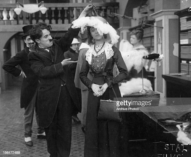 Charles Chaplin lifting hat of woman in a scene from the film 'The Floorwalker' 1916