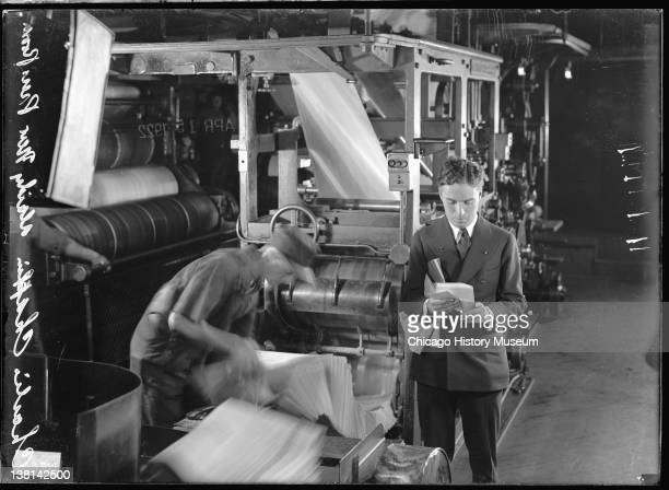 Charles Chaplin standing next to a man operating a newspaper press in the Chicago Daily News pressroom Chicago Illinois April 15 1922 From the...
