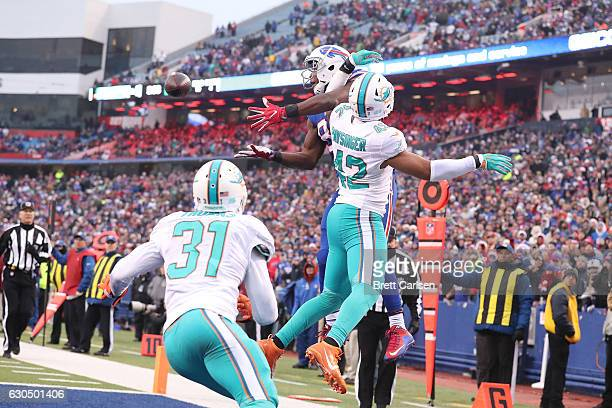 Charles Clay of the Buffalo Bills has a pass broken up by Spencer Paysinger of the Miami Dolphins during the second half at New Era Stadium on...