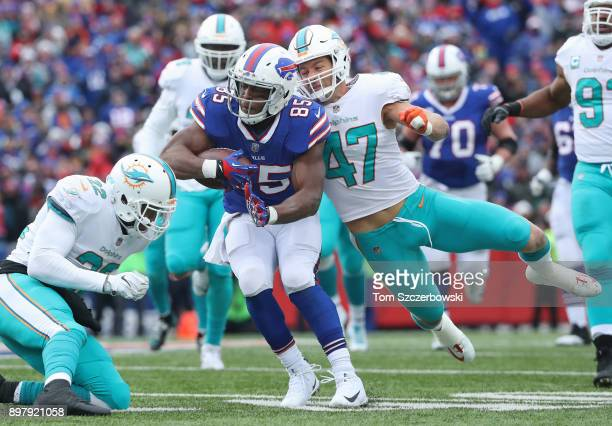 Charles Clay of the Buffalo Bills runs with the ball as he is tackled by Kiko Alonso of the Miami Dolphins and TJ McDonald during NFL game action at...