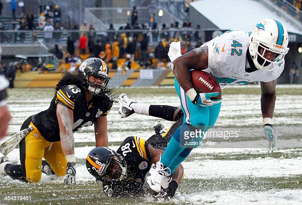 Charles Clay of the Miami Dolphins breaks a tackle against Troy Polamalu and Cortez Allen of the Pittsburgh Steelers to score a 12 yard touchdown...