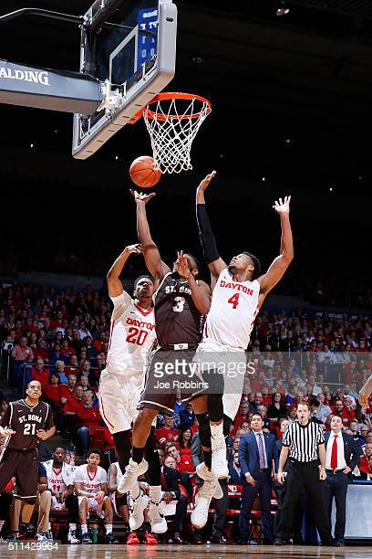 Charles Cooke and Xeyrius Williams of the Dayton Flyers defend against Marcus Posley of the St Bonaventure Bonnies in the first half of the game at...
