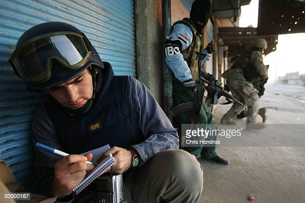 Charles Crain a reporter working for Time Magazine takes notes during a gun battle between insurgents and the 1st Battalion 5th Infantry Stryker...