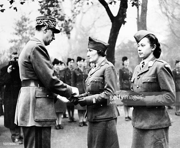 Charles de Gaulle , Chief of the French Free Forces, decorates French woman soldier and tenniswoman Simone Mathieu with the Croix de la Liberation in...