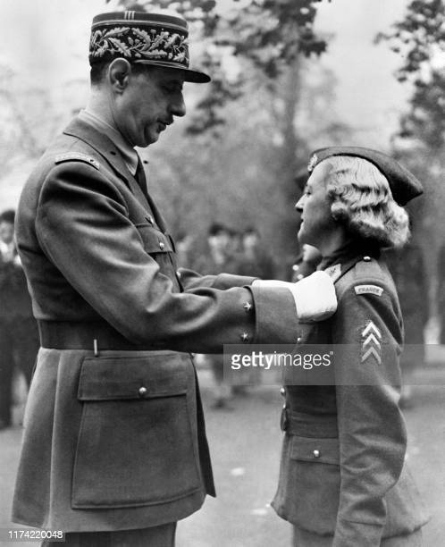 Charles de Gaulle Chief of the French Free Forces decorates French woman soldier Louisette Wagon with the Croix de Guerre in London on November 12...