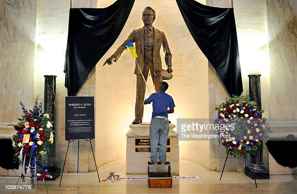 Charles Desmond spiffs up the statue of Senator Robert Byrd prior to the arrival of his casket which will lay in repose at the State Capitol in...