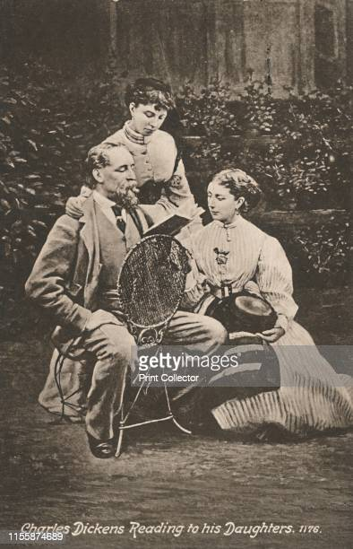 Charles Dickens Reading to his Daughters' 1865 British novelist Charles Dickens with his daughters Mary and Kate in the garden of his home Gad's Hill...