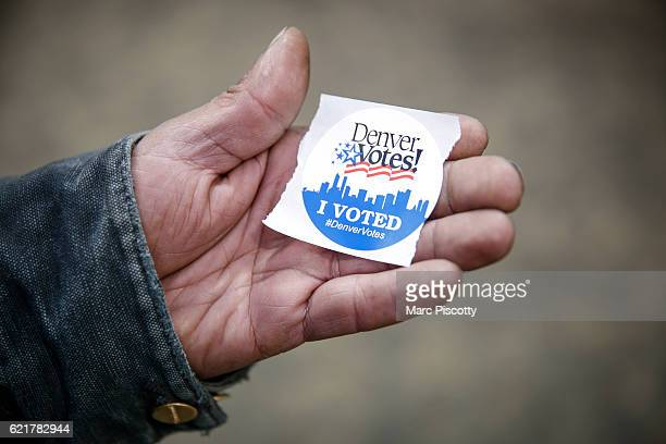 Charles Dominguez of Denver Colorado grabs an I Voted sticker after casting his ballot at the Denver Elections Division offices on November 8 2016 in...