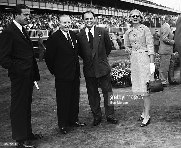 Charles E Wacker III John W Hanes Prince Aly Khan and CZ Guest standing close to the track at the Aqueduct Race Course NY c1959 Khan was the son of...