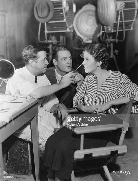 Charles Farrell watches a makeup artist at work on Marguerite Churchill his costar in the Paramount comedy 'Girl Without A Room'