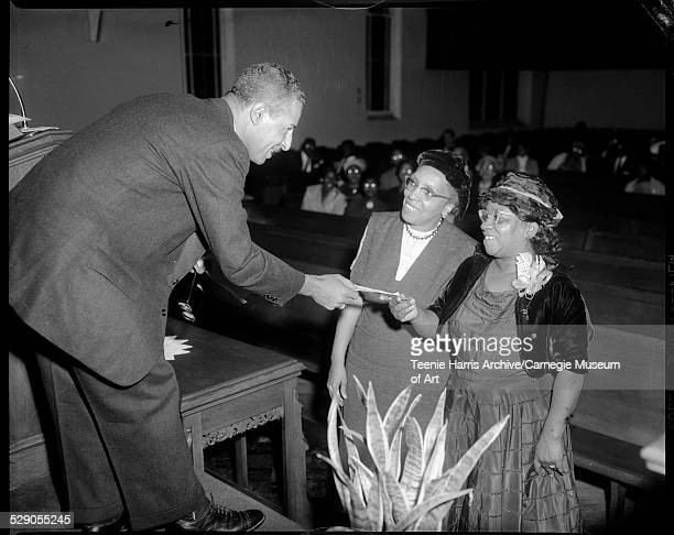 Charles Foggie receiving check from Annabelle Jefferson with Coretta Ogburn looking on in Ebenezer Baptist Church during NAACP membership meeting...