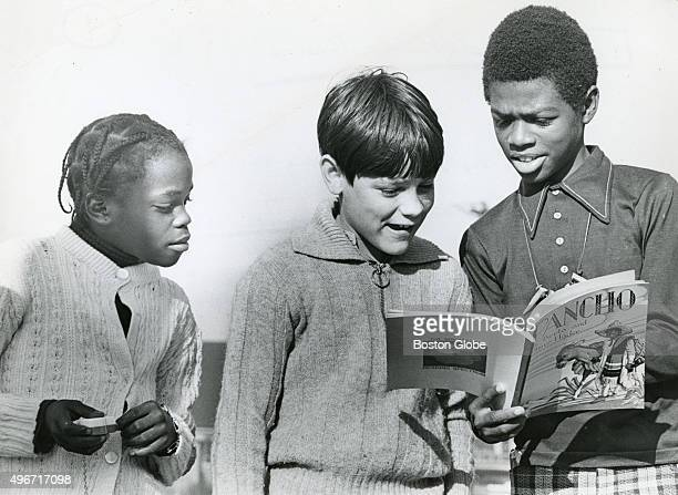 Charles Foye right of John W McCormack School shares his Pancho book with fellow John W McCormack School student Eddy Bogen Schutz center while...