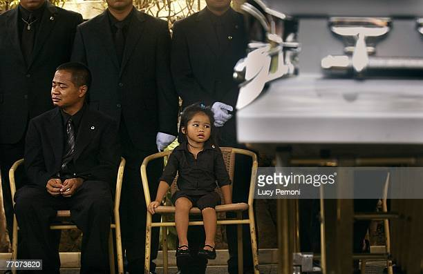 Charles Gagalac brother of Sgt Alexander Udarbe Gagalac of Wahiawa Hawaii and his neice JaceLynn Tolentino sit during Sgt Gagalac's burial at the...