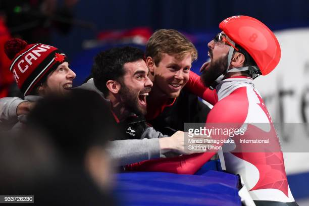 Charles Hamelin of Canada celebrates with brother Francois Hamelin and Pascal Dion in the men's 3000 meter SuperFinal during the World Short Track...