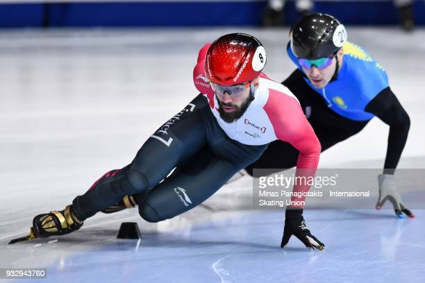 Charles Hamelin of Canada competes against Denis Nikisha of Kazakstan in the men's 1500 meter heats during the World Short Track Speed Skating...