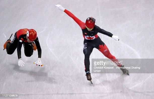 Charles Hamelin of Canada corsses the finish line before Ren Ziwei of China during the men 5000 meter relay final A during the ISU Short Track World...