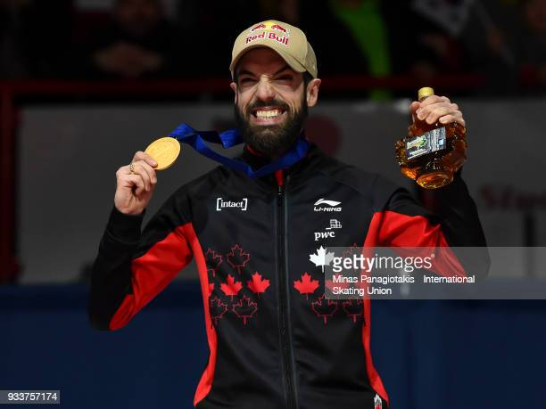 Charles Hamelin of Canada holds up his gold medal after finishing first in the men's 1000 meter Final during the World Short Track Speed Skating...