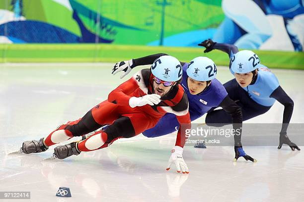 Charles Hamelin of Canada leads from Sung SiBak of South Korea and Simon Cho of the United States in the Men's 500m Short Track Speed Skating...