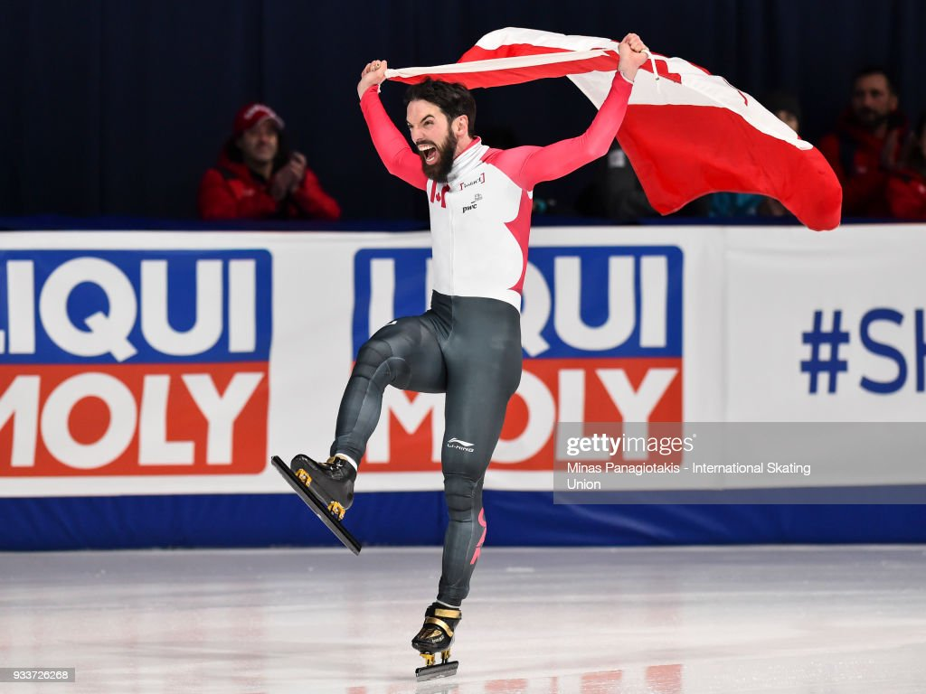 Charles Hamelin of Canada raises the Canadian flag after becoming the overall champion in the men's 3000 meter SuperFinal during the World Short Track Speed Skating Championships at Maurice Richard Arena on March 18, 2018 in Montreal, Quebec, Canada.